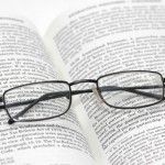 Reading glasses with light frame over the open book